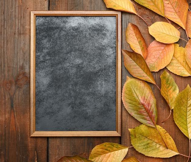 Quadro-negro de madeira vazio com folhas de outono