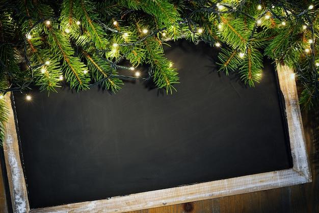 Quadro-negro decorado com galhos de pinheiro e luzes de natal
