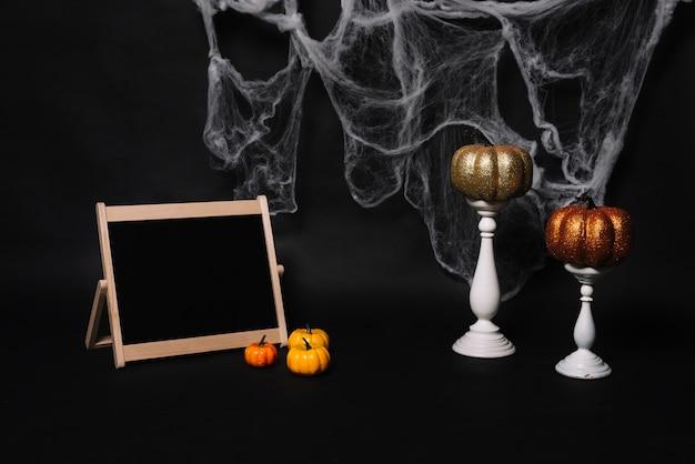 Quadro-negro e abóboras perto de velas e web