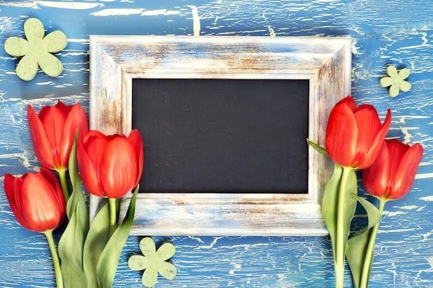 Quadro-negro e bando de tulipas vermelhas e flores de lírio do vale no azul rústico, espaço