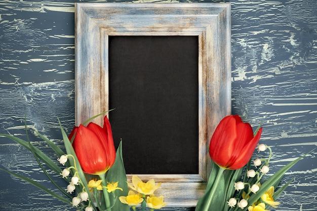 Quadro-negro e monte de tulipas vermelhas e flores de lírio do vale em fundo rústico