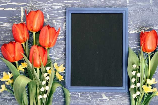 Quadro-negro e ramo de tulipas vermelhas e flores de lírio do vale na superfície rústica