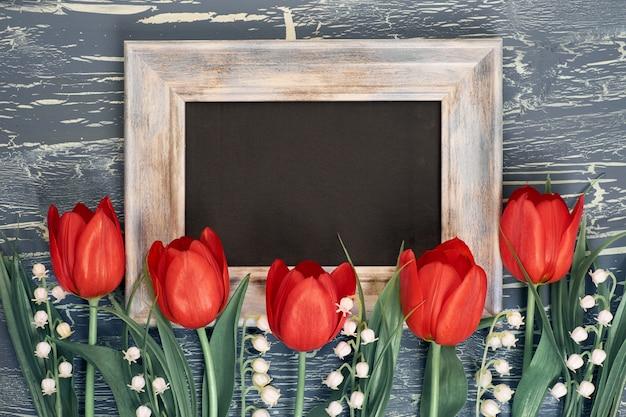 Quadro-negro e ramo de tulipas vermelhas e flores de lírio do vale