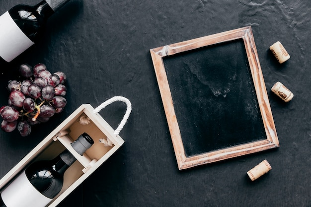 Quadro-negro e rolhas perto de garrafas e uva