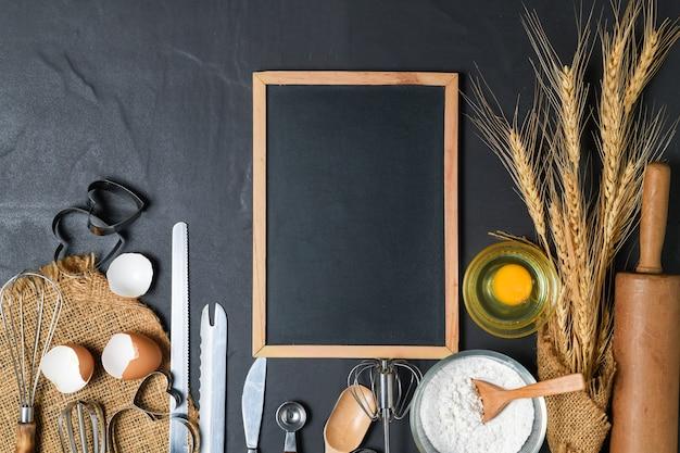 Quadro-negro em branco e ovos frescos, farinha de bolo com utensílios de cozinha para bolos na mesa preta, espaço de cópia para texto do menu de entrada