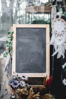 Quadro-negro em frente ao café com flores decoradas ao redor