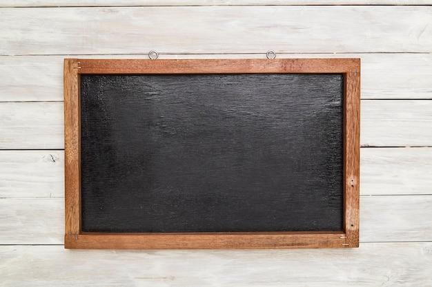Quadro negro em moldura de madeira na parede de madeira