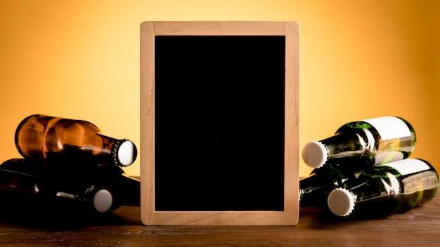 Quadro-negro entre conjunto de garrafas alcoólicas na mesa de madeira