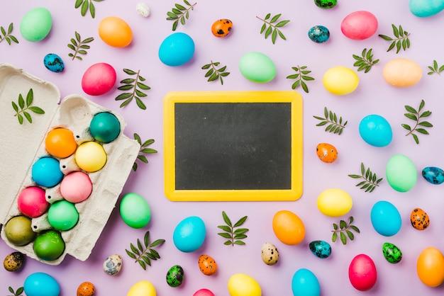 Quadro-negro entre conjunto de ovos coloridos e folhas perto de recipiente