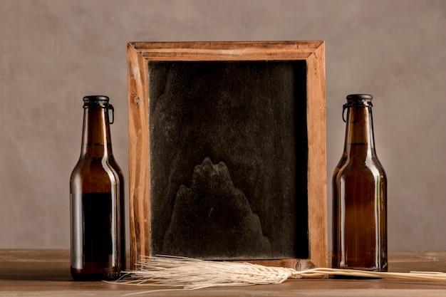 Quadro-negro entre duas garrafas de cerveja na mesa de madeira