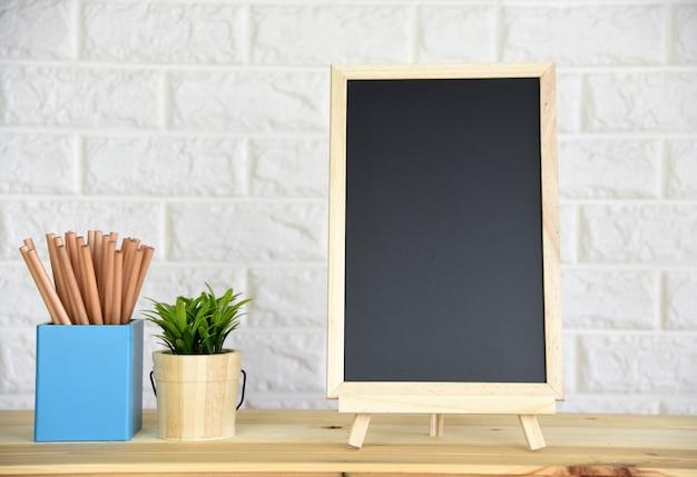 Quadro negro na mesa de madeira, com espaço para seu texto.
