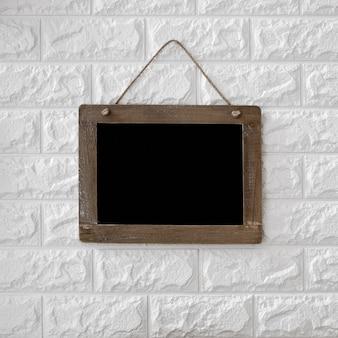 Quadro-negro no fundo da parede de tijolo texturizado