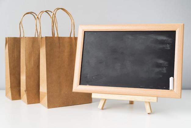 Quadro-negro perto de sacolas de compras