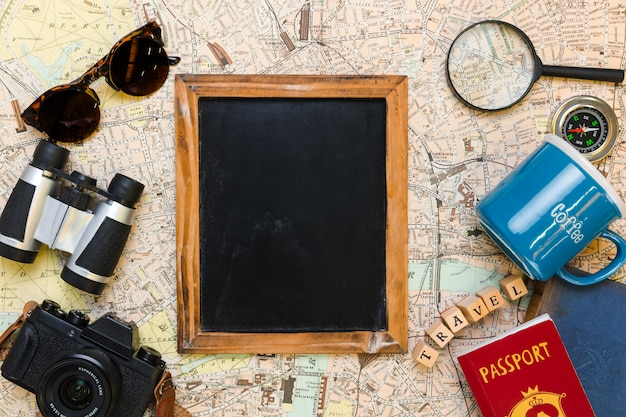 Quadro-negro rodeado por elementos de viagem
