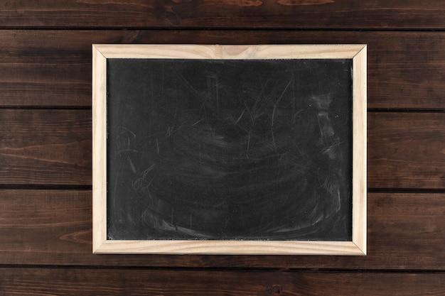 Quadro negro sujo em uma moldura em um fundo escuro de madeira, espaço de cópia, vista superior