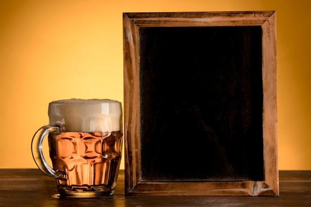 Quadro-negro vazio com copo de cerveja na mesa de madeira