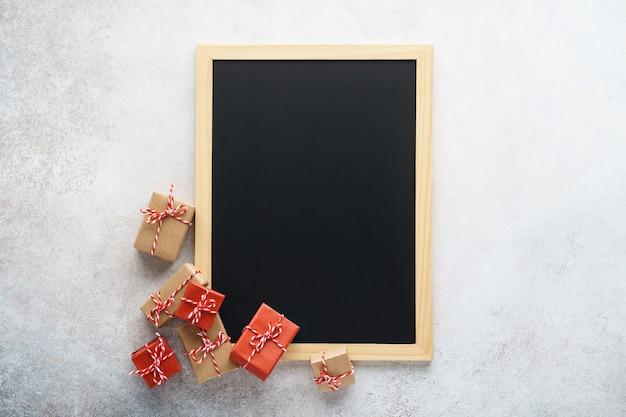 Quadro-negro vazio e várias caixas de presente em cinza claro