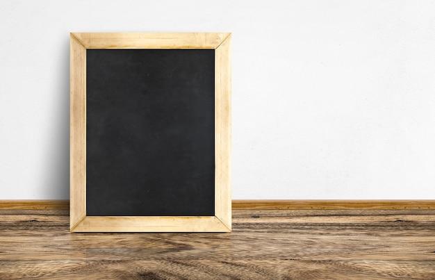 Quadro-negro vazio encostado no piso de madeira rústico e parede branca