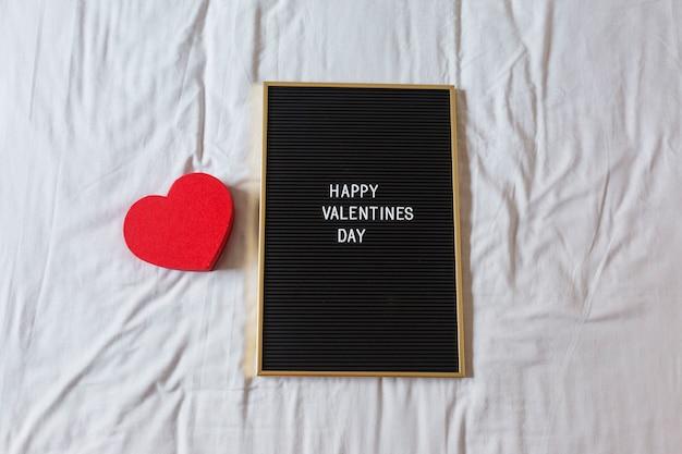 Quadro-negro vintage com mensagem feliz dia dos namorados e um coração vermelho com fundo. casa, dentro de casa. conceito