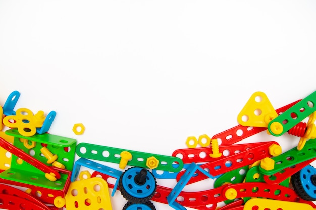 Quadro para texto. a vista superior da construção multicolorido do brinquedo das crianças obstrui tijolos no fundo branco.