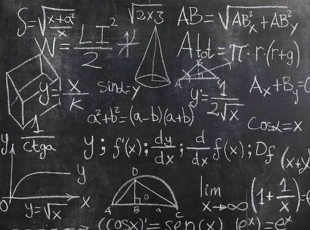 Quadro preto com fórmulas matemáticas e problemas