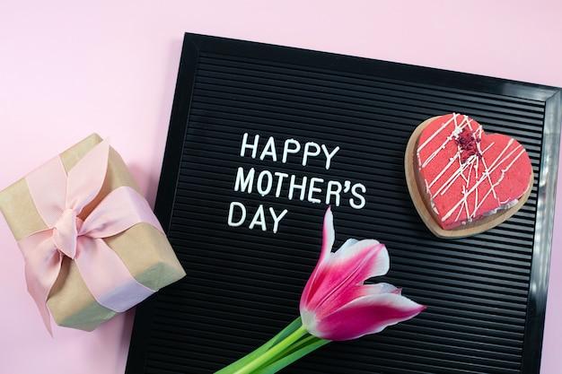 Quadro preto com letras de plástico brancas com citação. feliz dia das mães