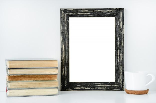 Quadro preto isolado com as decorações do copo branco e de livros velhos.