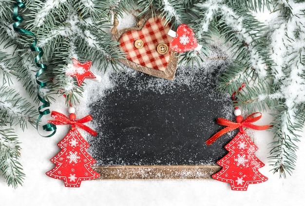 Quadro preto na neve decorada para o natal, espaço de texto