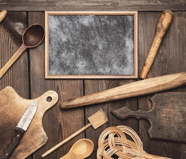 Quadro preto vazio e itens vintage de cozinha de madeira: rolo, colheres vazias, faca, tábua de cortar na mesa de madeira marrom, vista superior