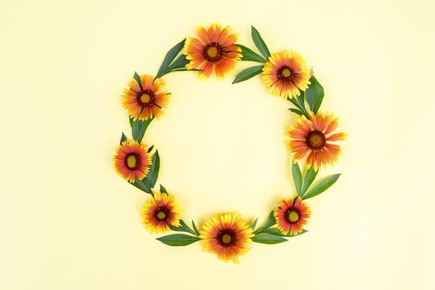 Quadro redondo de flores amarelo-laranja sobre um fundo claro. composição floral espaço para texto, plana leigos. fundo de primavera.