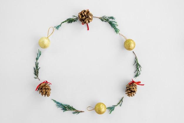 Quadro redondo de natal feito de pinhas, ramos de pinheiro e bolas de ouro em background branco
