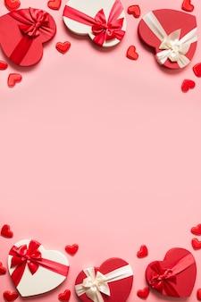 Quadro romântico de dia dos namorados de presentes com corações vermelhos em fundo rosa. postura plana. cartão vertical com espaço de cópia.