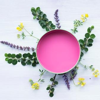 Quadro vazio rosa circular decorado com folhas e flores em plano de fundo texturizado de madeira