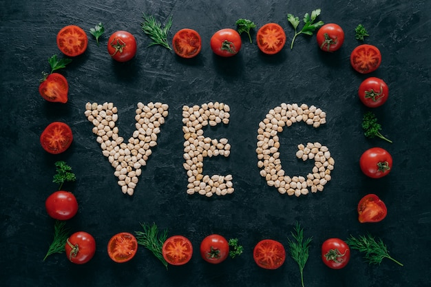 Quadro vegetal feito de tomate e salsa verde, endro. carta em forma de grão-de-bico no meio.