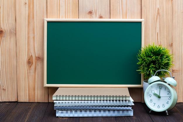 Quadro verde em branco pequena árvore despertador e notebook na madeira