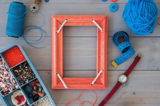 Quadro vermelho; carretel; fita métrica; relógio de pulso; lã e miçangas em caixa azul na mesa de madeira