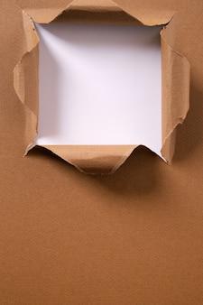 Quadro vertical de fundo rasgado buraco quadrado de papel marrom