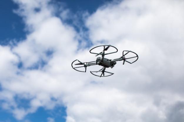 Quadrocopter contra o céu azul com nuvens brancas.