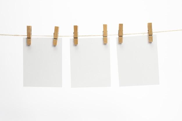 Quadros de papel vazios que penduram em uma corda com prendedores de roupa e isolados no branco. cartões em branco na corda.