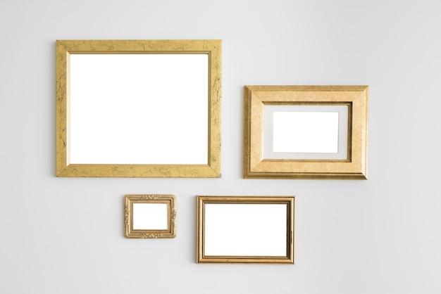 Quadros dourados vazios em branco na parede branca.