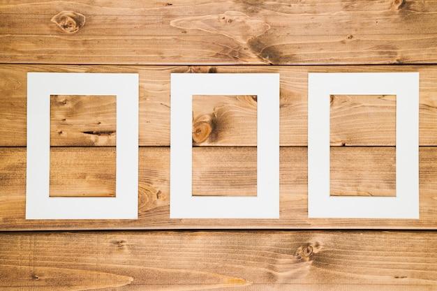 Quadros vazios brancos com fundo de madeira