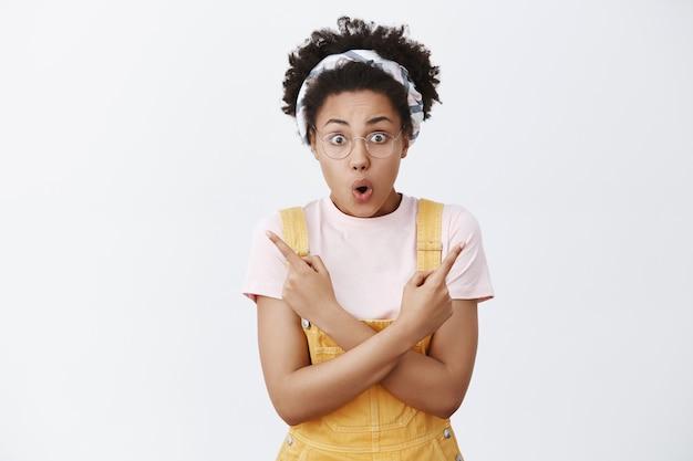 Qual caminho certo. garota afro-americana atraente chocada e surpresa, amigável, de óculos, bandana e macacão, apontando com as mãos cruzadas em diferentes direções, tentando escolher entre uma variedade de opções