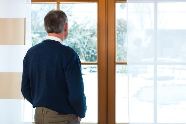 Qualidade de vida - idoso ou aposentado em casa em frente à janela, aproveitando a aposentadoria ou pensão por idade