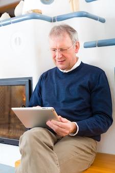 Qualidade de vida - idoso ou pensionista sentado em casa em frente ao forno, escrevendo e-mails no tablet ou lendo um e-book