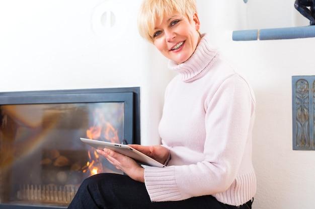 Qualidade de vida - mulher idosa ou aposentada sentada em casa em frente ao forno, escrevendo e-mails no tablet ou lendo um e-book
