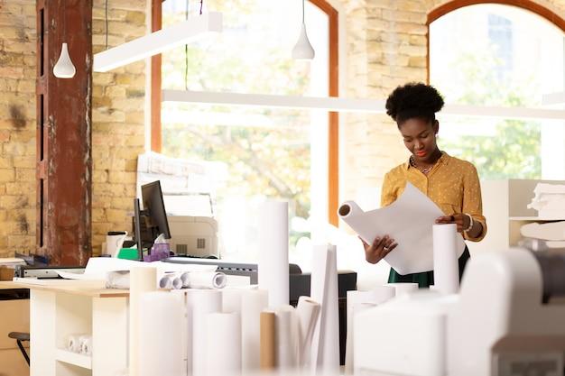Qualidade do papel. trabalhador diligente de pele escura de agência de publicação verificando a qualidade do papel