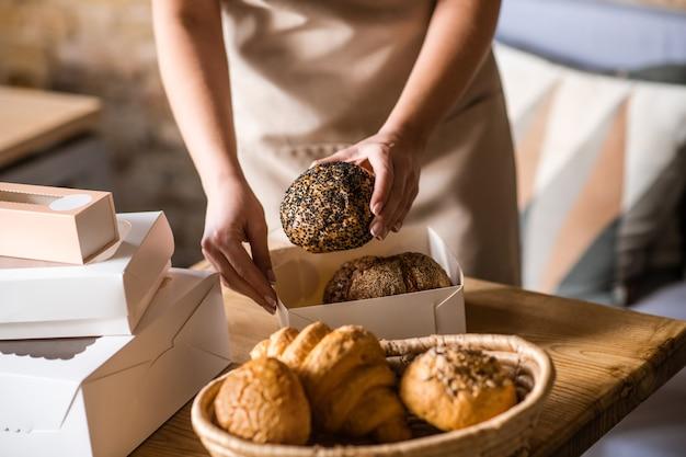 Qualidade impecável. belas mãos femininas embalando cuidadosamente o pão de forma na caixa da padaria, sem rosto