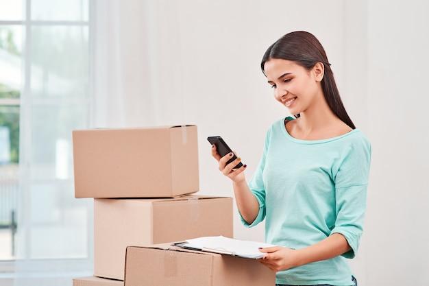 Qualquer momento é um bom momento para começar uma jovem mulher preparando pacotes para Foto Premium