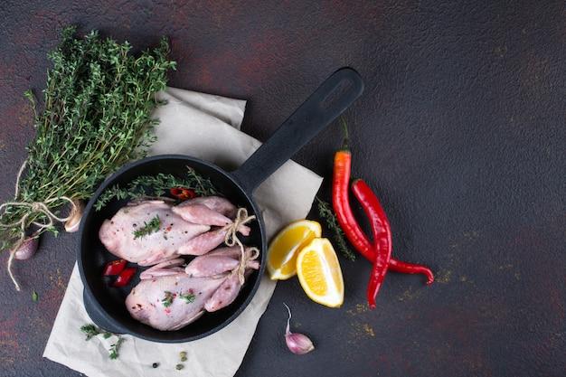 Quals crus pequenos com algum tempero pronto para cozinhar na panela redonda preta.