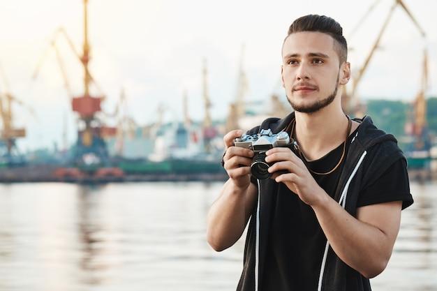 Quando o hobby se torna um trabalho amado. retrato de sonhador jovem criativo com barba segurando a câmera e olhando de lado com expressão satisfeita pensativa, tirando fotos do porto e do mar enquanto caminhava